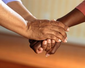 elderly person holding hands combating loneliness
